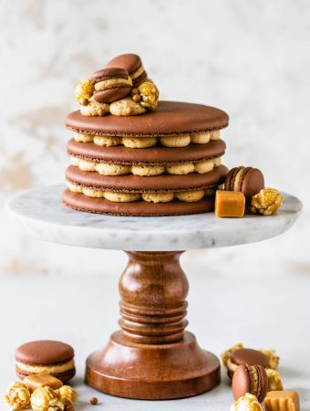 Caramel Macaron Cake layers of chocolate macaron shells filled with caramel buttercream topped with mini macarons, caramel popcorn.