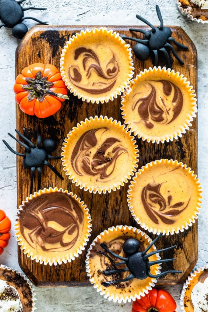 Chocolate Pumpkin Mini Cheesecakes on top of a board, with fondant spiders and mini pumpkins around.