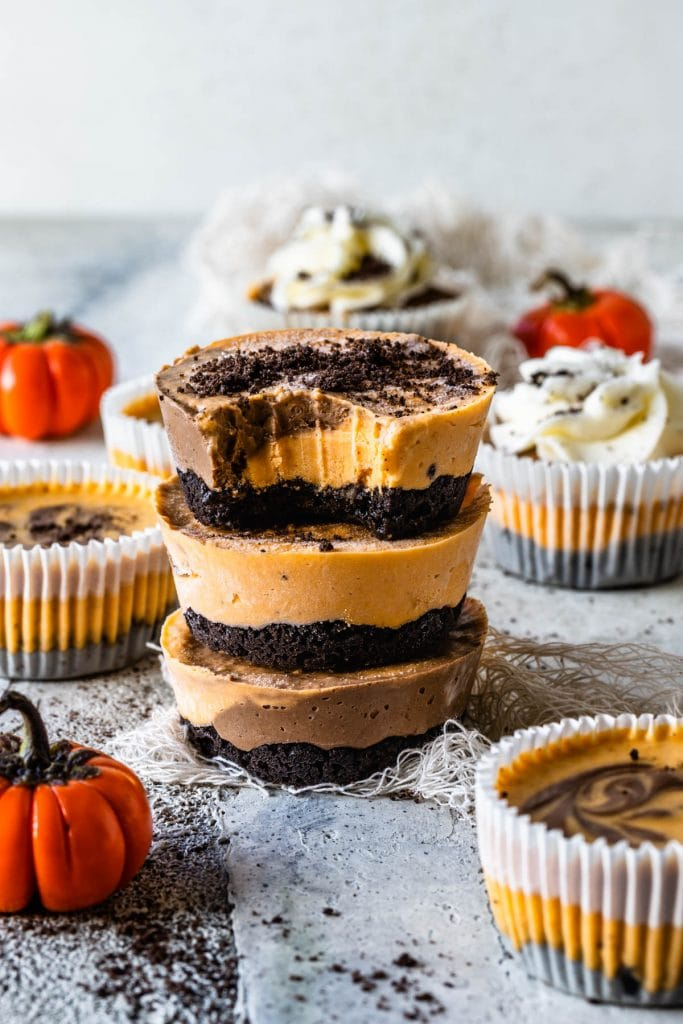 Chocolate Pumpkin Mini Cheesecakes stacked, the first cheesecake has a bite taken out of it. Around there are pumpkins and more mini cheesecakes decorating. they are topped with oreo crumbs and the cheesecakes on the back are topped with whipped cream.