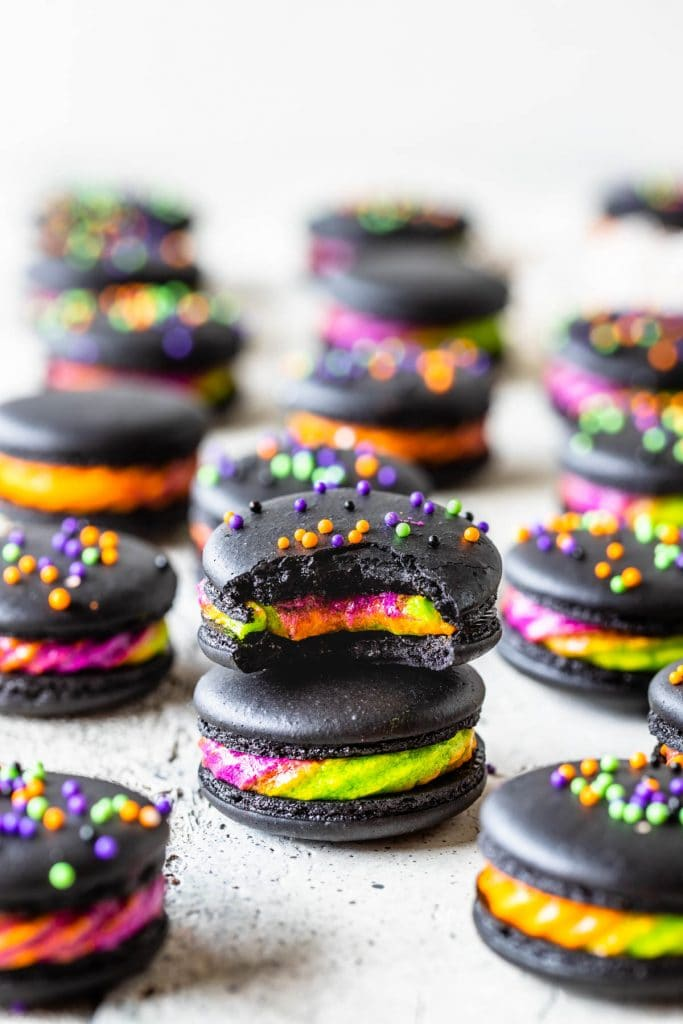 halloween Macarons stacked filled with a purple, green and orange frosting, topped with colorful sprinkles, with a bite taken out.