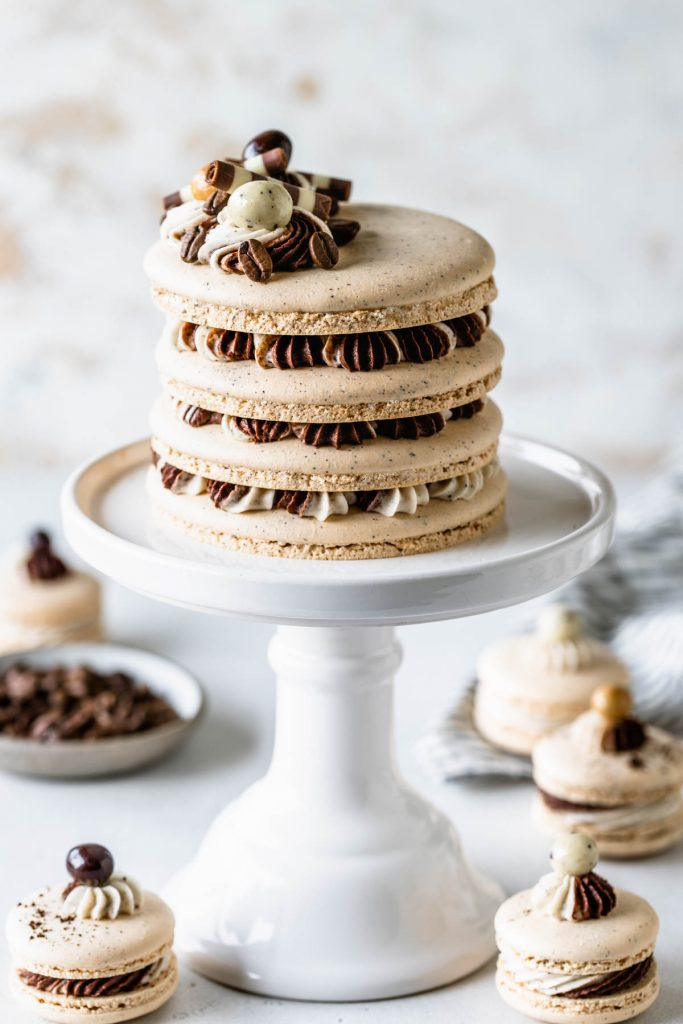 Coffee Macaron Cake, macaron shells filled with mocha and espresso frosting, topped with frosting, chocolate covered espresso beans.