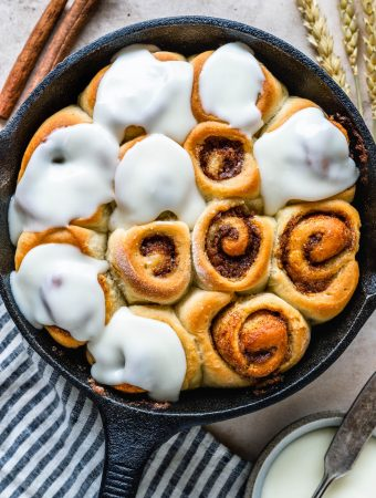 Mini Cinnamon Rolls in a skillet, topped with cream cheese frosting.