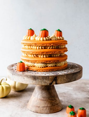 Pumpkin Caramel Macaron Cake topped with pumpkin candy corns on top of a cake stand.