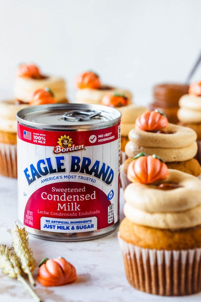 Dulce de Leche Pumpkin Cupcakes topped with a little pumpkin and with a russian buttercream next to a can of eagle brand® sweetened condensed milk.
