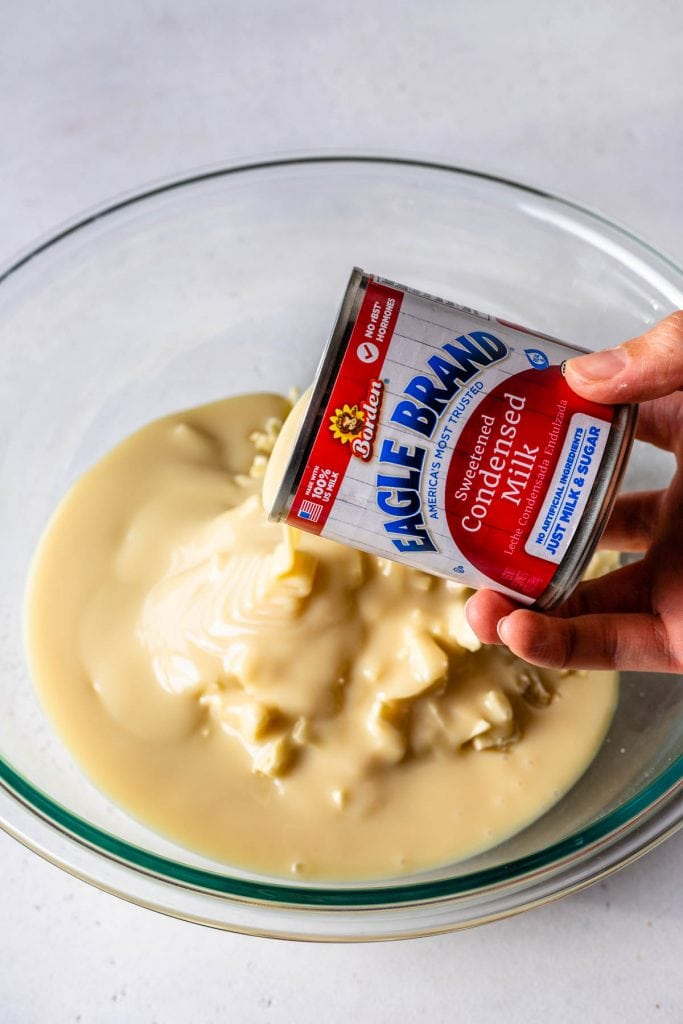 pouring condensed milk over chocolate.