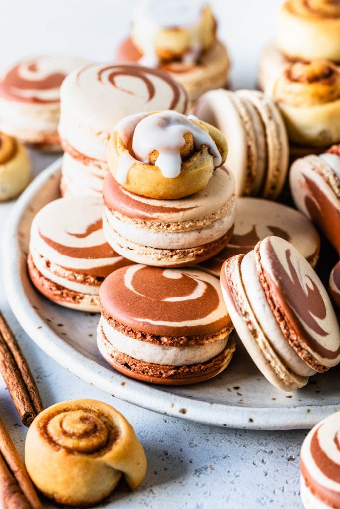 macarons on a plate, with swirl shells, and also topped with mini cinnamon rolls.