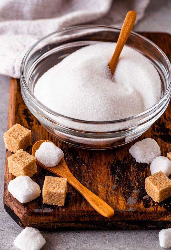 a bowl with sugar and a spoon, and sugar cubes on the side.