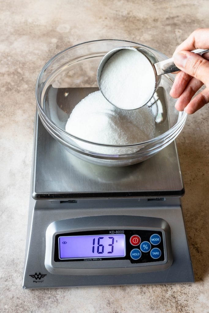 a bowl on top of a scale and a hand pouring sugar inside the bowl.