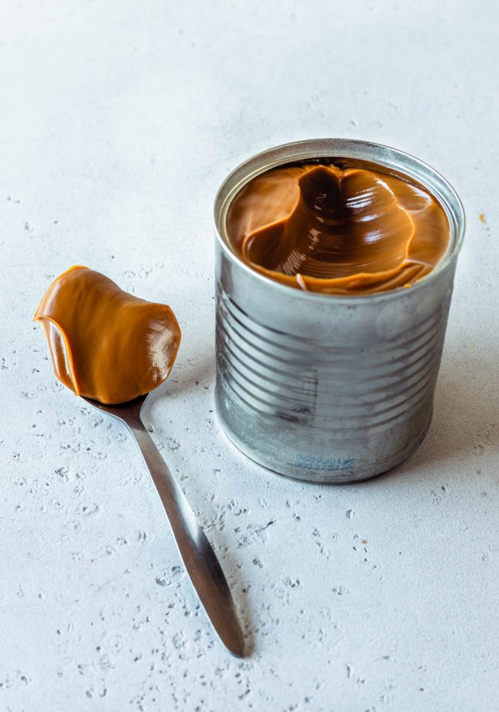 condensed milk can with instant pot dulce de leche inside with a spoon on the side.