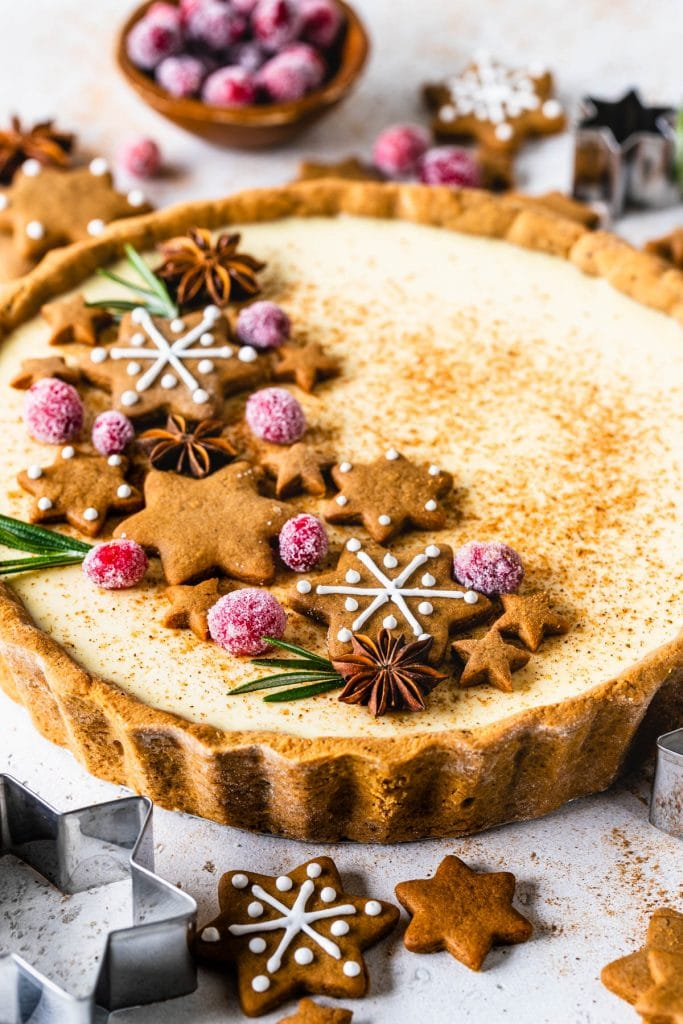 christmas pie filled with eggnog filling and gingerbread crust, topped with gingerbread cookies, sugared cranberries and rosemary sprigs.