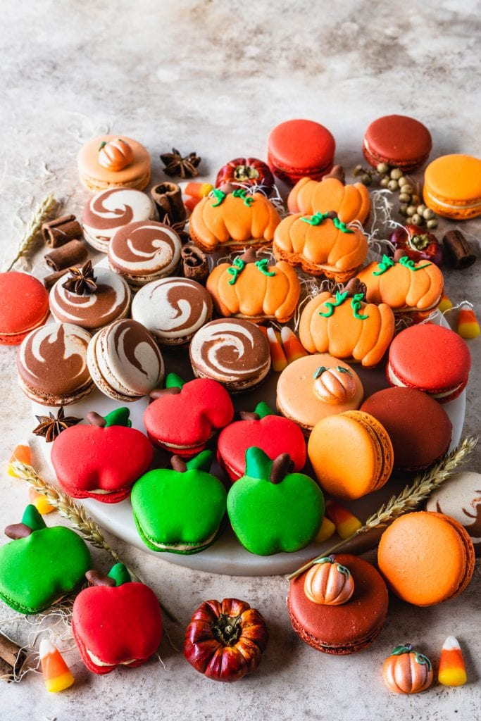 board with lots of different varieties of macarons, pumpkin, cinnamon roll, apple, and caramel pumpkin.