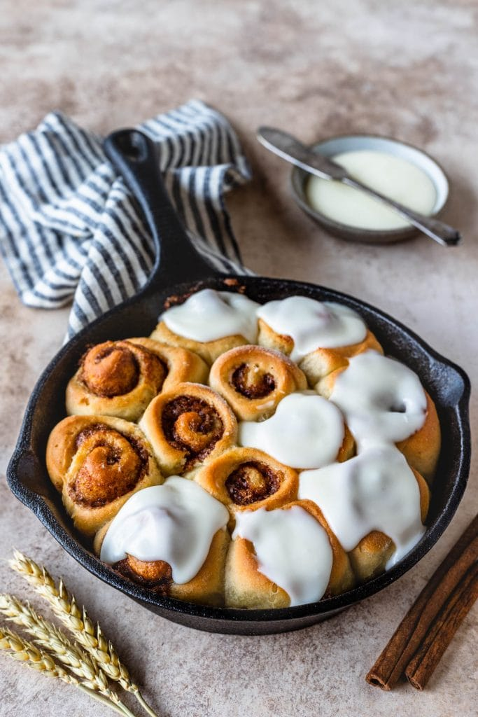 cinnamon rolls in a skillet topped with cream cheese frosting.