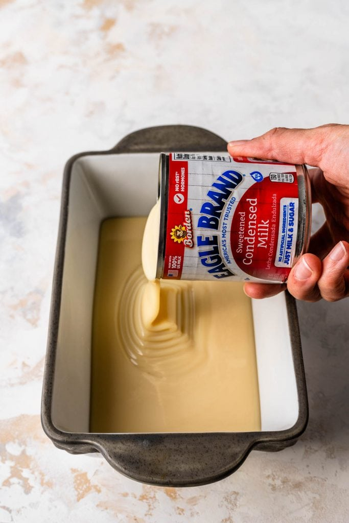 pouring a can of condensed milk inside of a loaf pan.