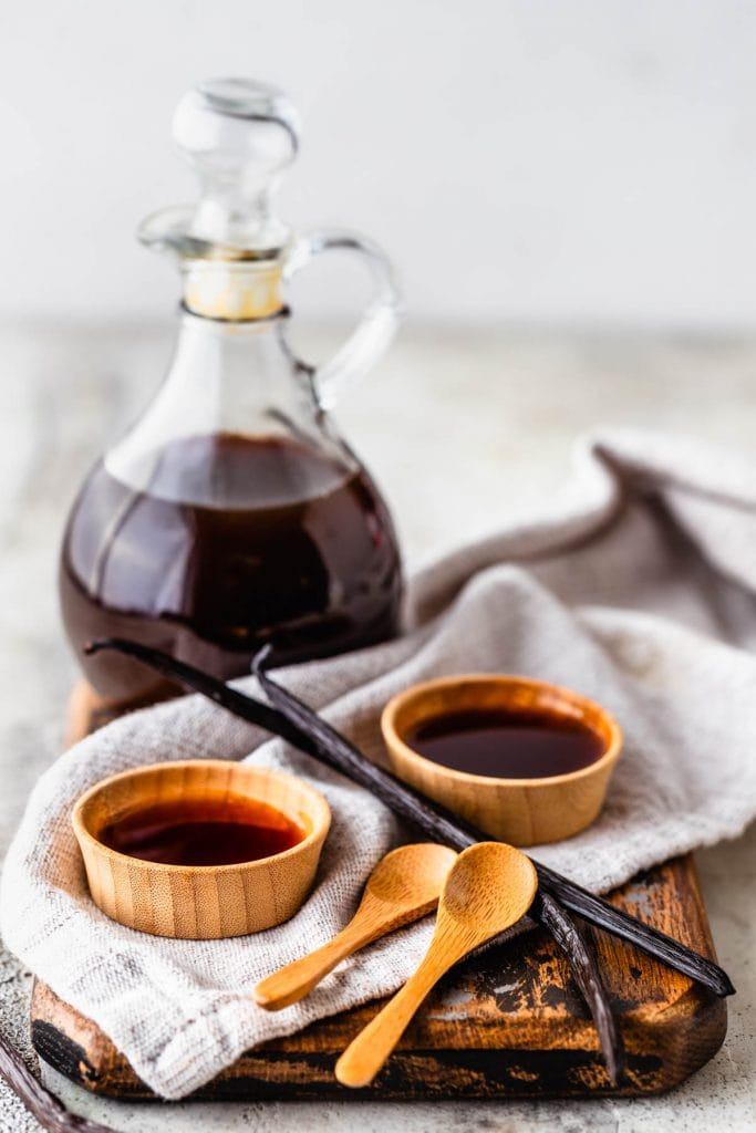 Vanilla extract in a container, with two saucers filled with vanilla, two wooden spoons around, vanilla bean pods.