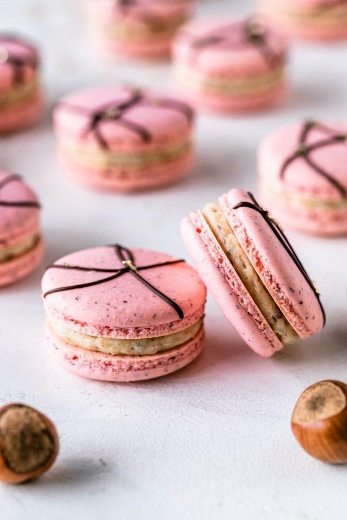 Hazelnut Macarons pink macaron shells with a chocolate decoration on top.
