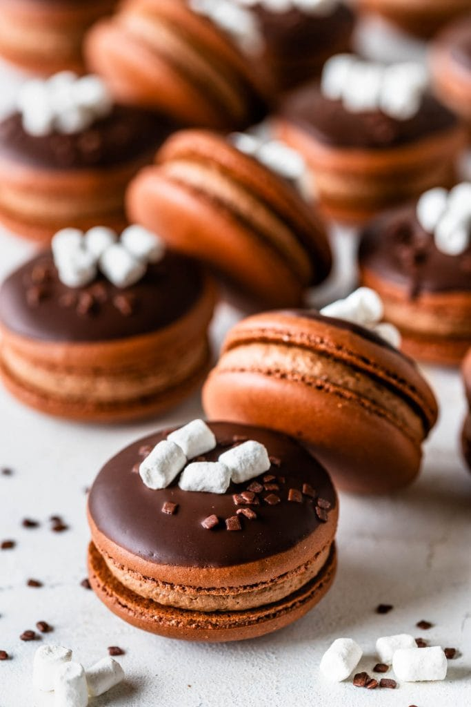 Hot Cocoa Macarons topped with melted chocolate and marshmallows and sprinkles.