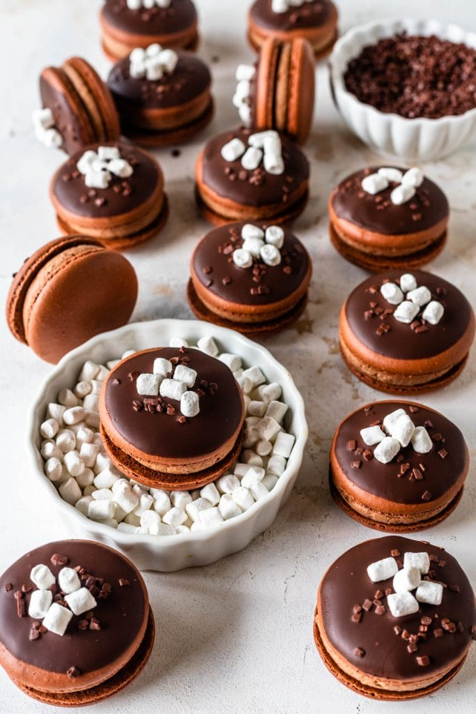 Hot Chocolate Macarons topped with melted chocolate and marshmallows and sprinkles.