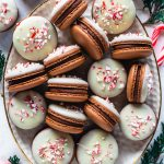 Peppermint Bark Macarons on a plate topped with white chocolate and crushed candy canes.