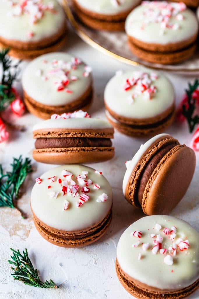 peppermint macarons filled with peppermint ganache, topped with melted white chocolate and crushed peppermint candy canes.