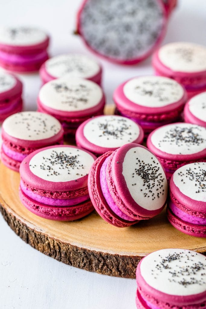Pitaya macarons with a bicolor shell, pink and white, and with poppy seeds on top to resemble dragon fruit.