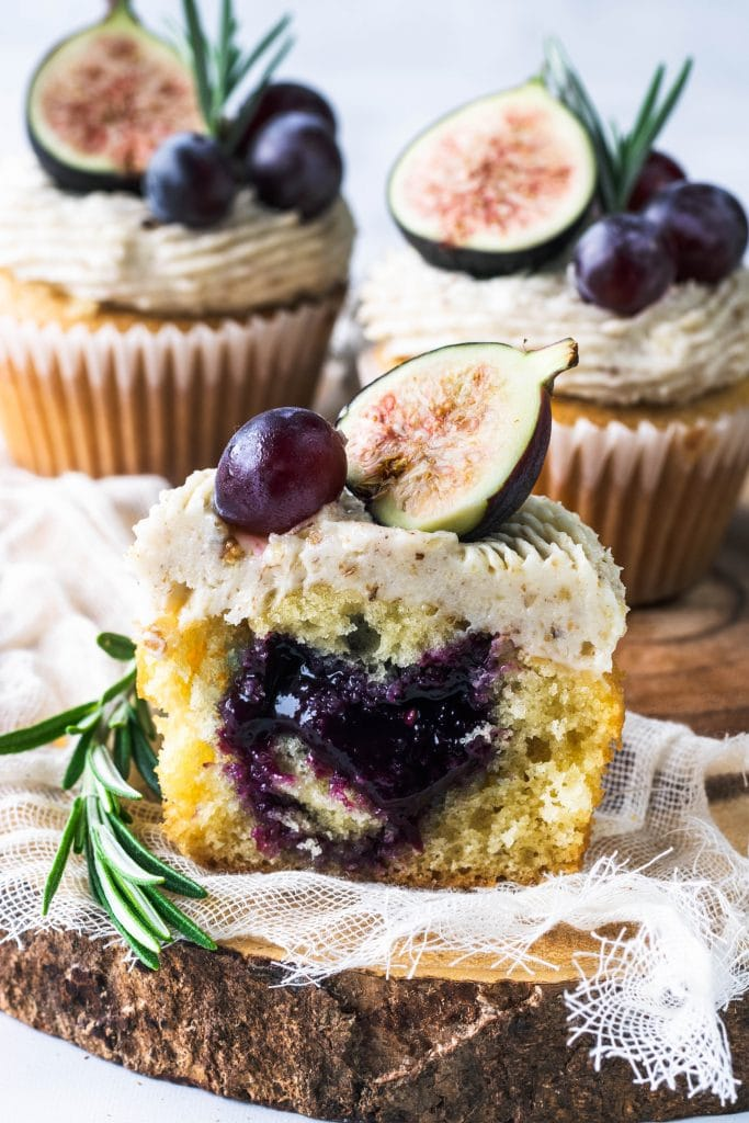 grape cupcakes filled with grape jam, sliced in half, topped with grapes and fig.