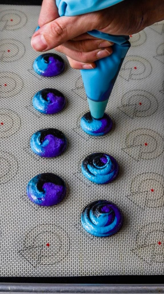 piping bag piping galaxy macarons on a silicone mat.