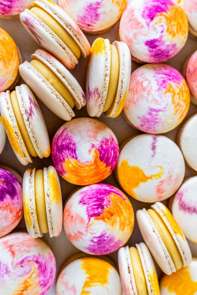 passionfruit macarons with a tie dye macaron shell filled with passionfruit ganache.