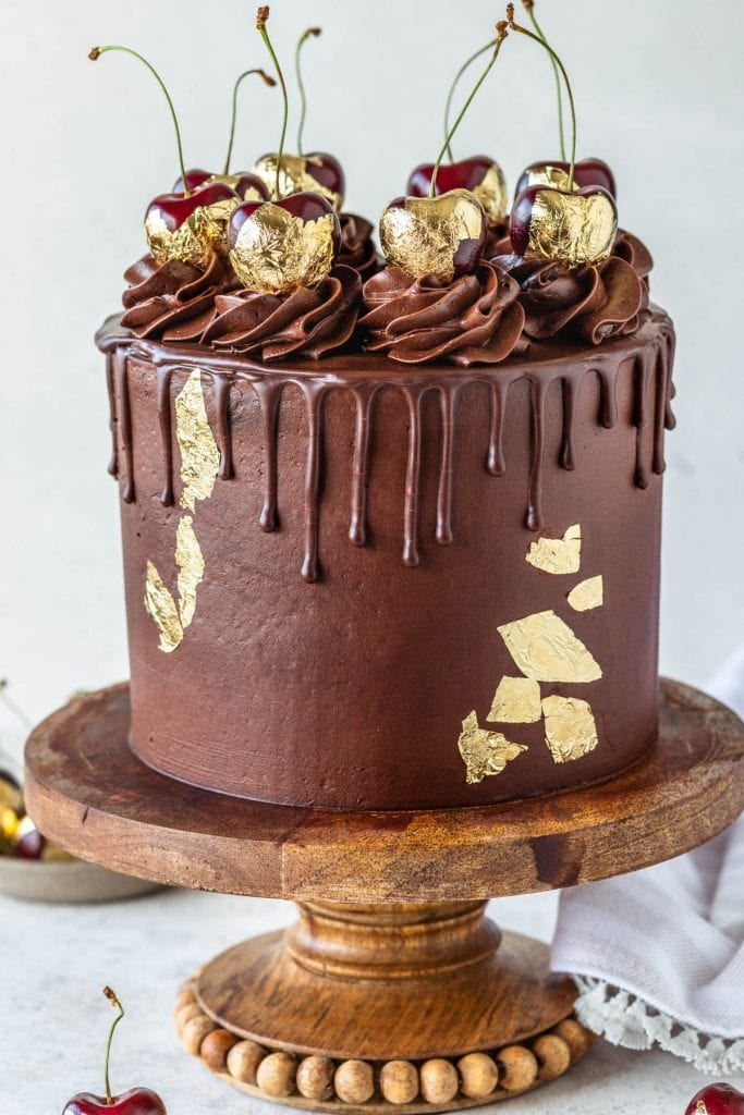 Chocolate Cherry Cake topped with chocolate pudding frosting and gold cherries
