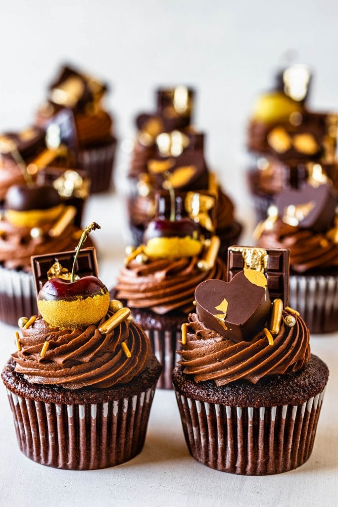 chocolate cupcakes filled with biscoff, topped with biscoff chocolate frosting, decorated with cherries dipped in gold, chocolate bars, chocolate hearts and gold sprinkles.