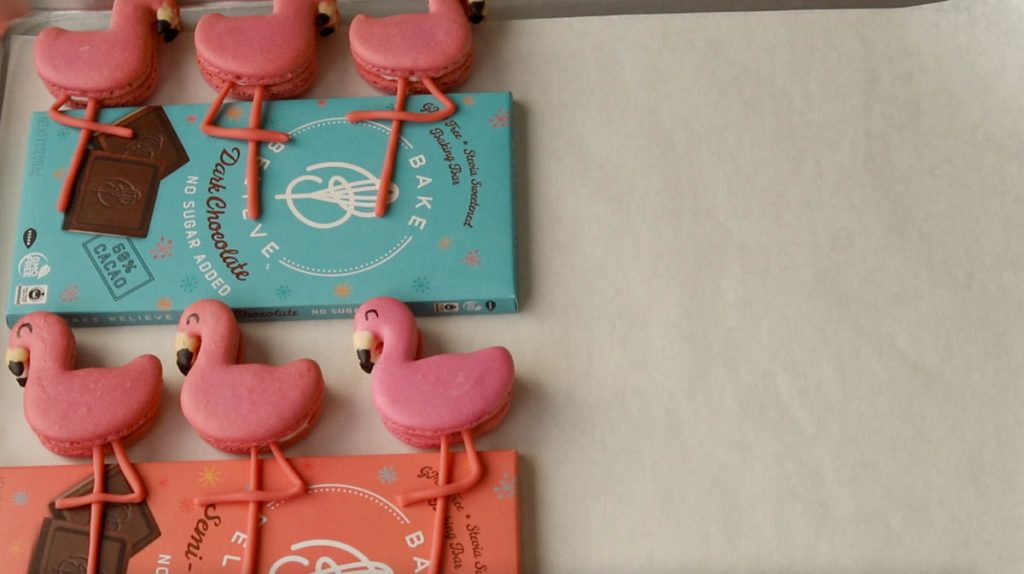 macarons shaped like flamingos resting so the legs will dry.