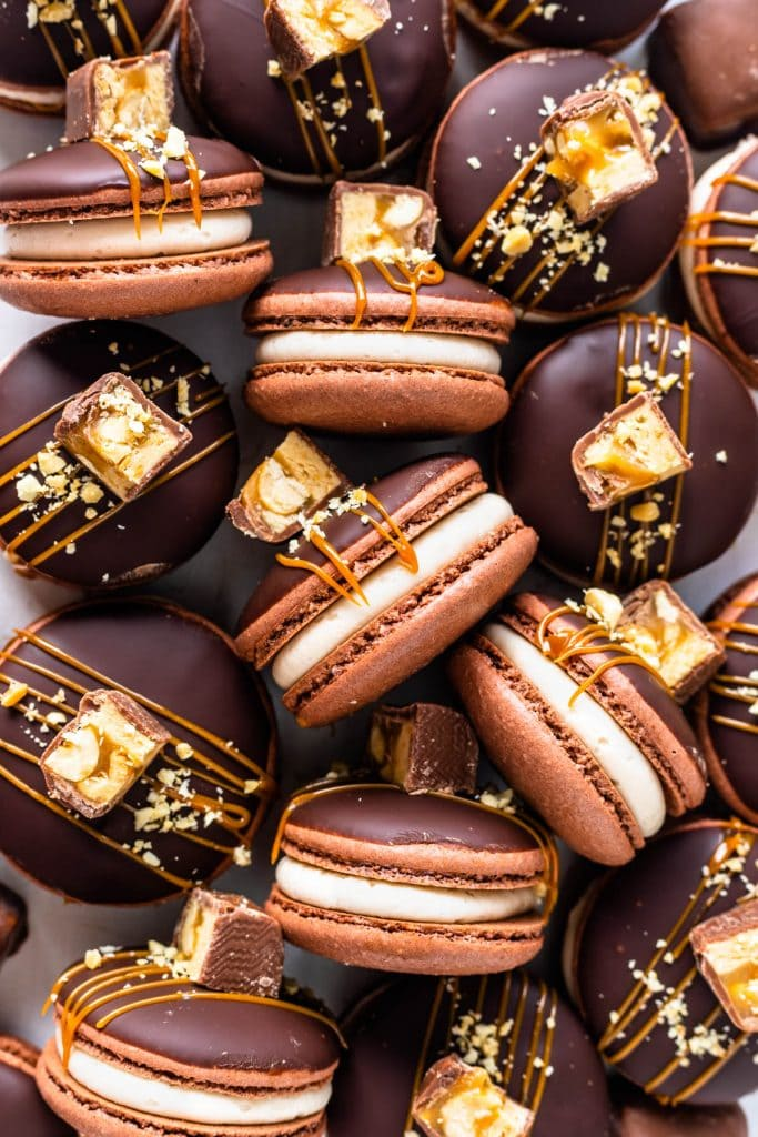 Snickers macarons filled with salted caramel, topped with caramel sauce and chopped snickers candy.