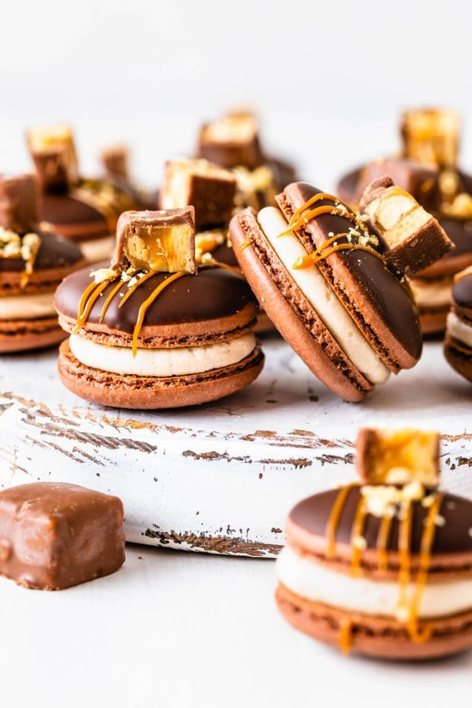 chocolate macarons filled with salted caramel, topped with caramel sauce and chopped snickers candy.