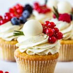 cupcakes frosted with White Chocolate Buttercream topped with lindt lindor truffles, red currants, and berries.