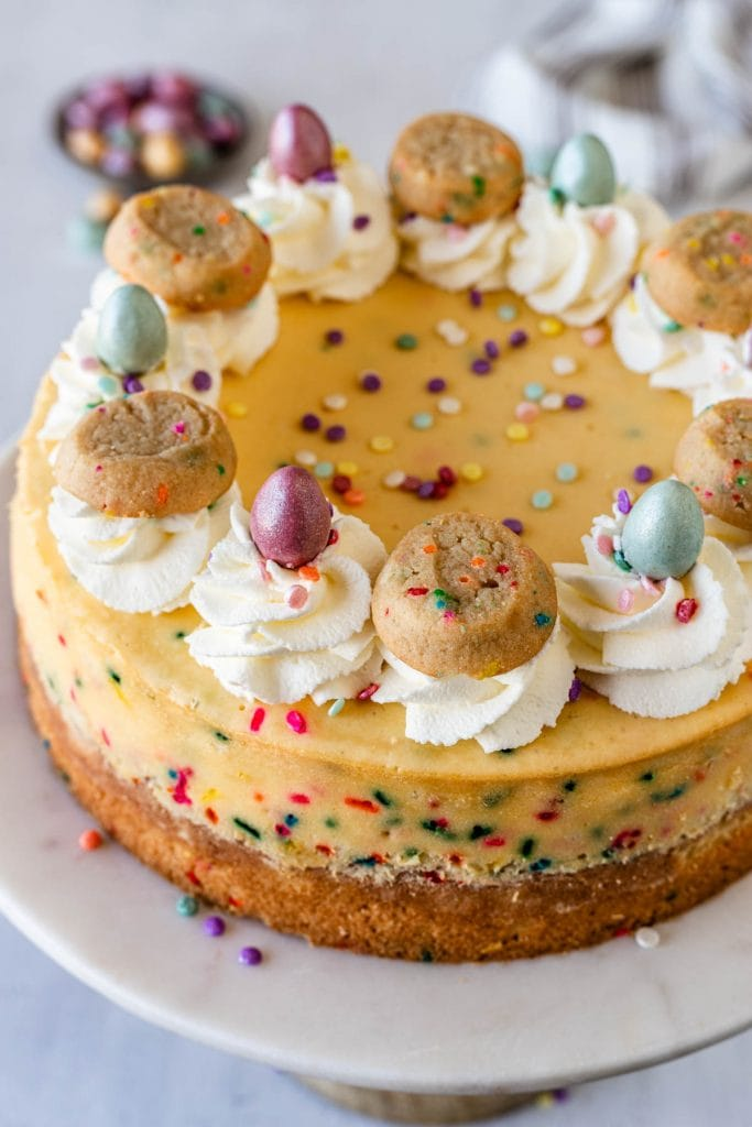 funfetti cheesecake topped with cookies and chocolate eggs.