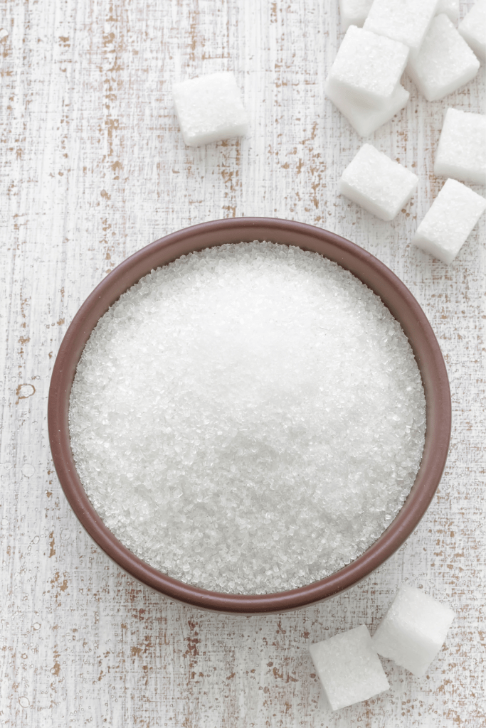 bowl of sugar with sugar cubes next to it.