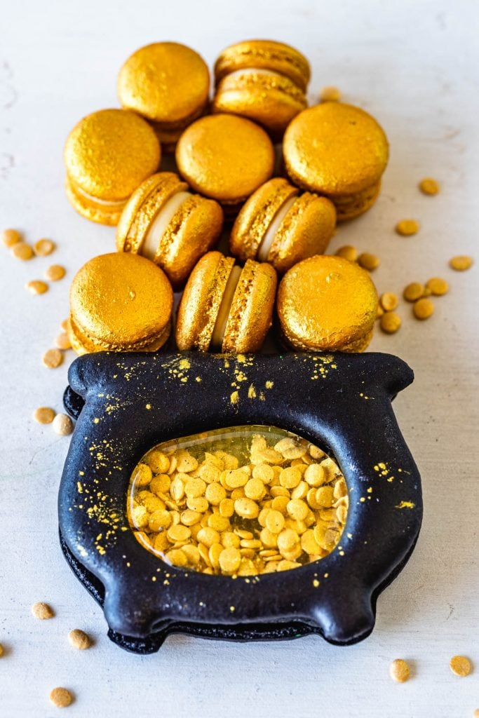 pot of gold shaped macaron filled with gold sprinkles and with mini gold macarons on top.