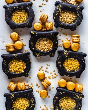 macarons shaped like pots of gold, filled with gold sprinkle coins, and with mini gold macarons.