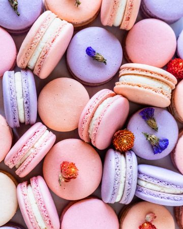 purple, pink, and peach color macarons with flowers.