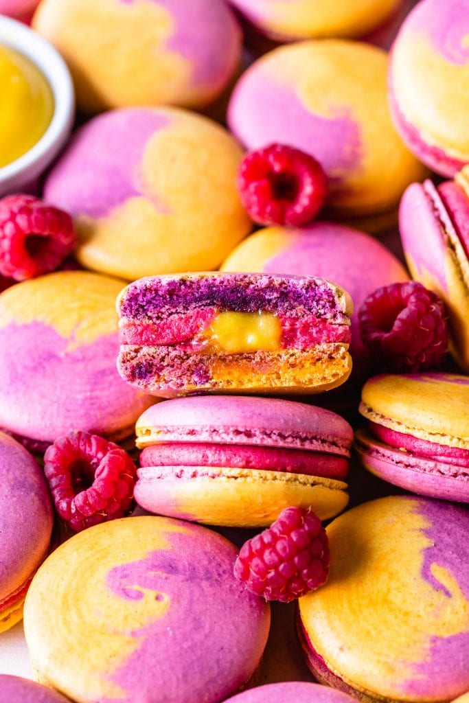 Mango Raspberry Macarons with bicolor shells pink and yellow sliced in half showing the mango curd and raspberry buttercream filling.