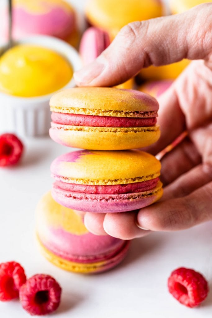 hand holding a stack of two yellow and pink macarons.