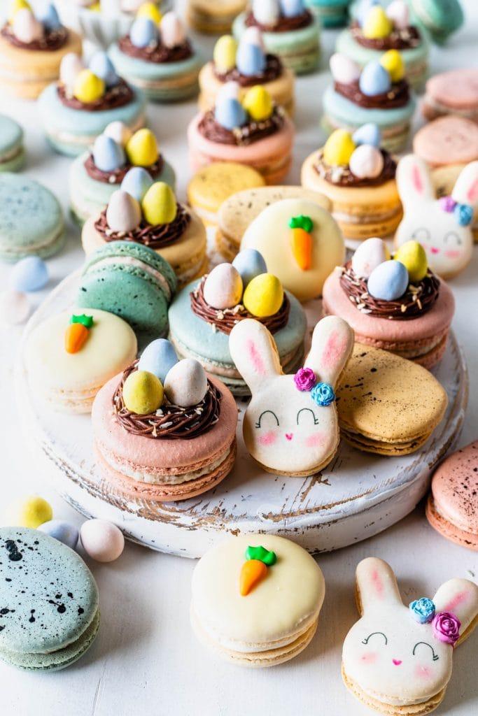 spread of easter macarons, macarons shaped like bunnies, carrot macarons, nest macarons, and robins eggs macarons.