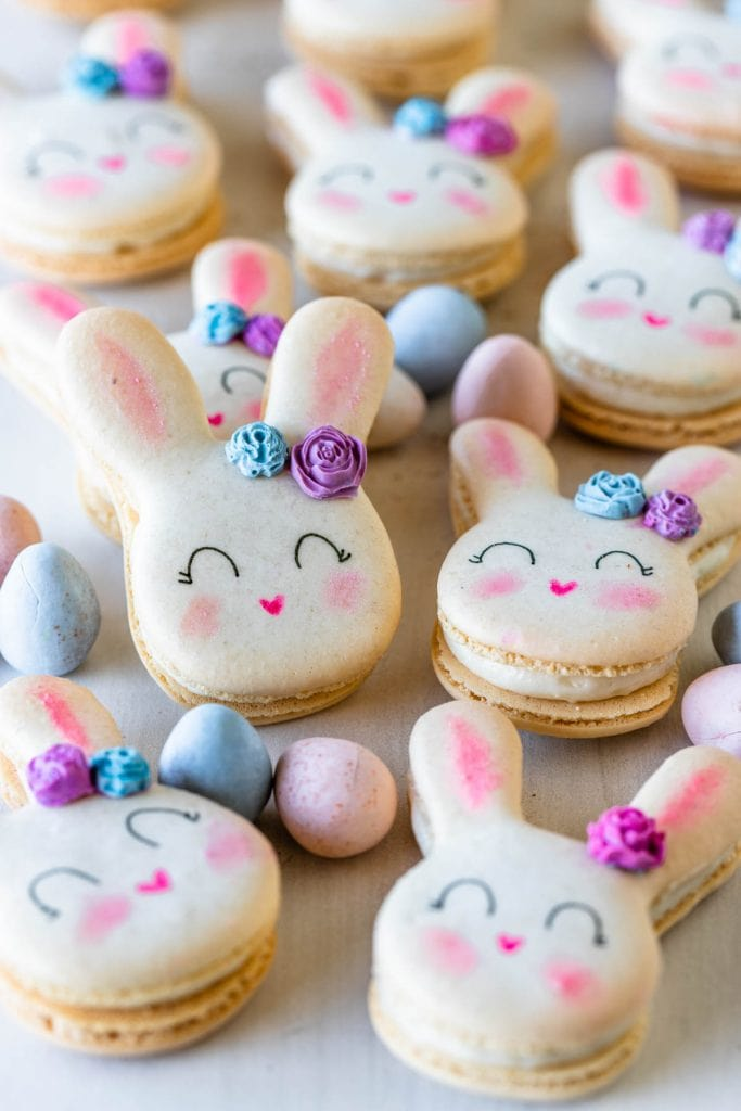 bunny shaped macarons with a little chocolate rose in the ear, on a plate with cadbury eggs.