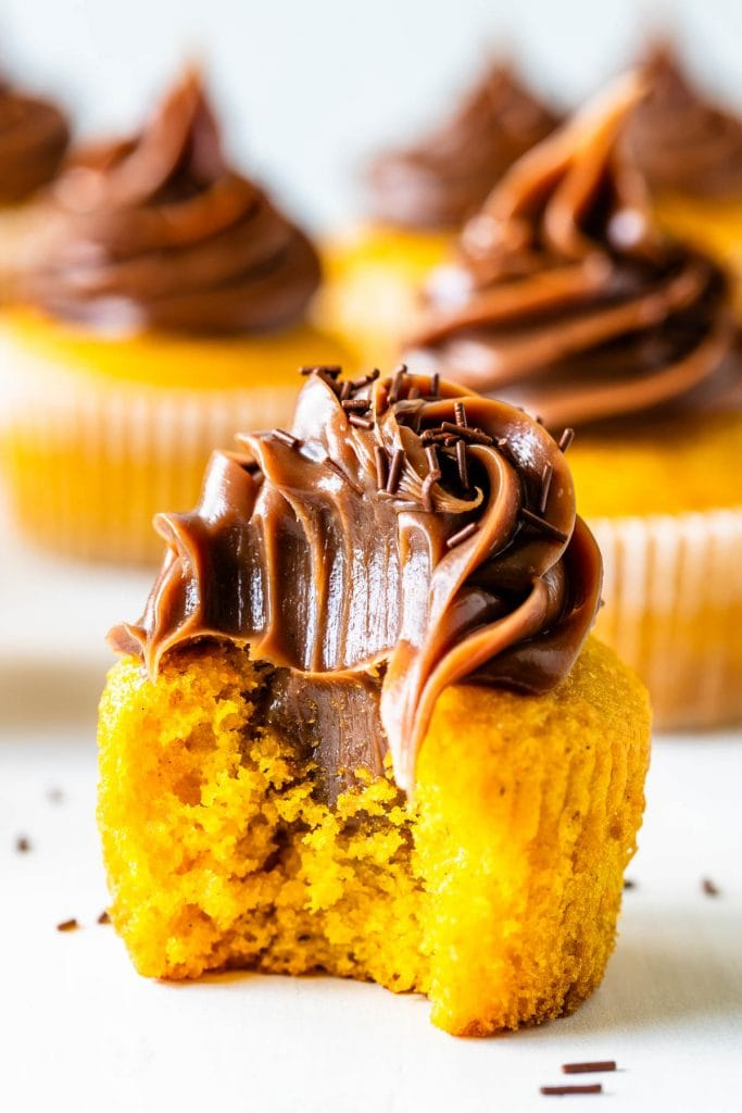 Carrot cupcakes topped with brigadeiro bit in half.