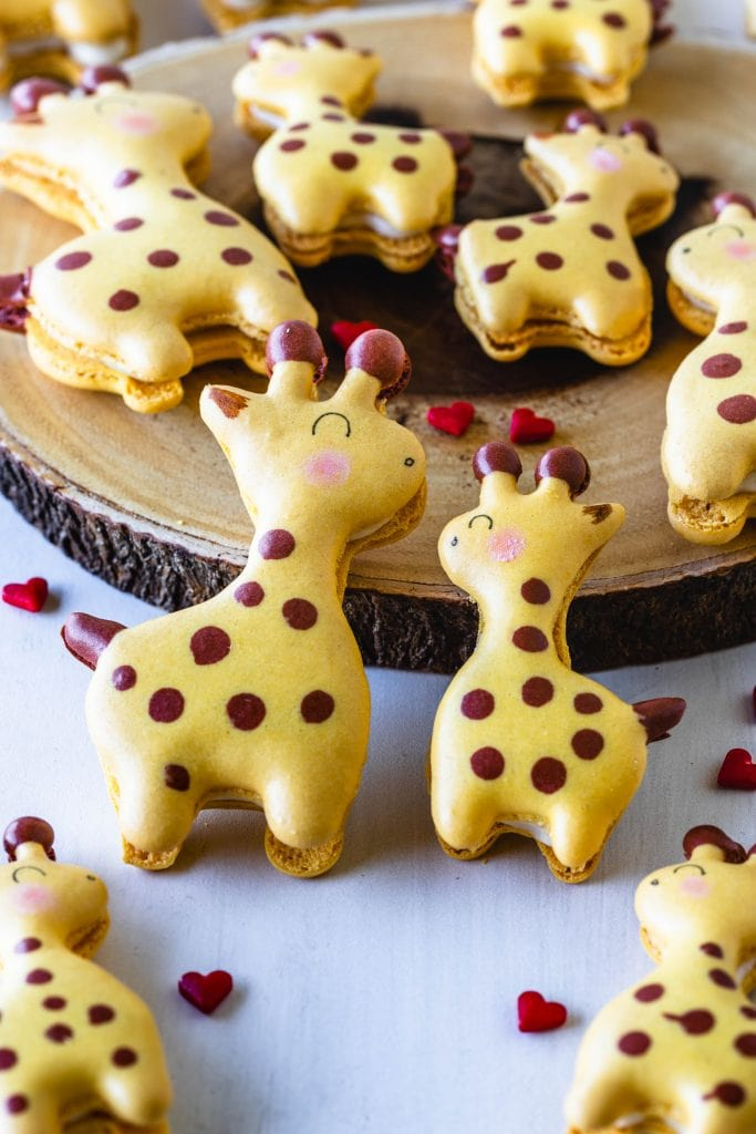 Giraffe Macarons with heart sprinkles around, and a mama and a baby giraffe.
