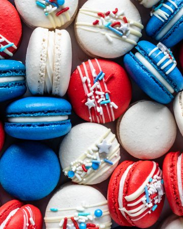Red White and Blue Macarons topped with a white chocolate drizzle and sprinkles.