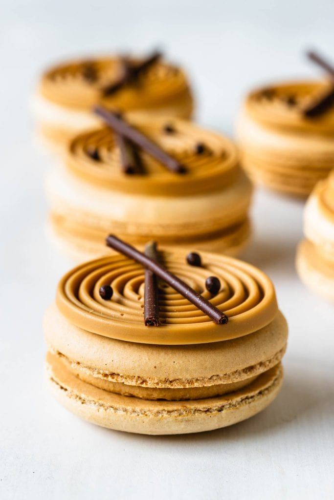 amarula macarons topped with a blonde chocolate swirl decoration and chocolate curls.