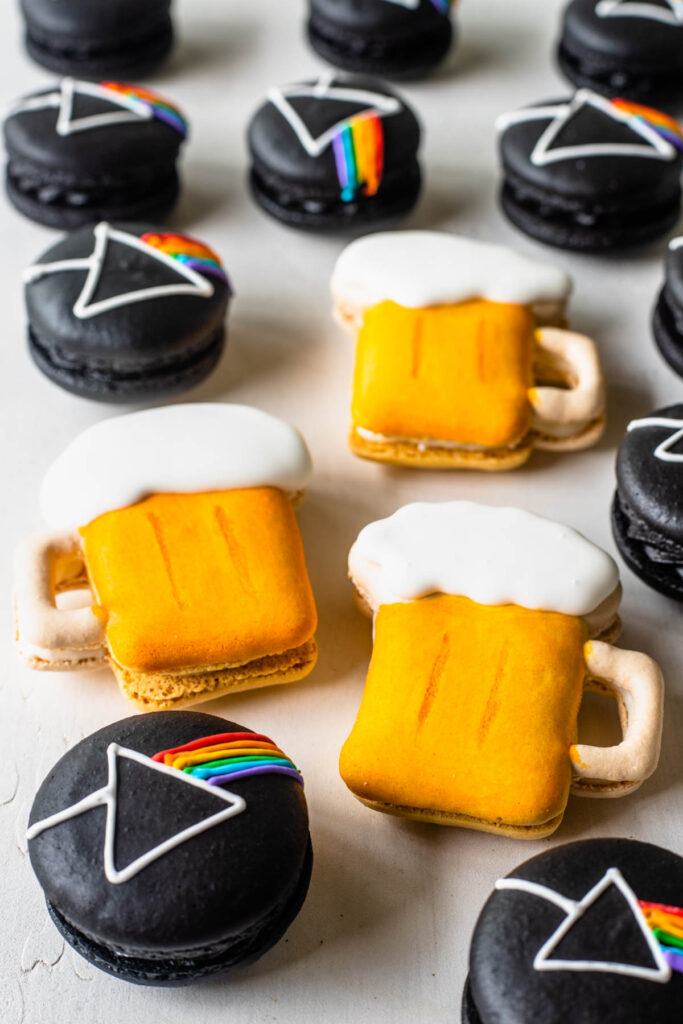 Pink Floyd Macarons, black macarons with the pink floyd logo drawn on top with royal icing next to beer macarons.