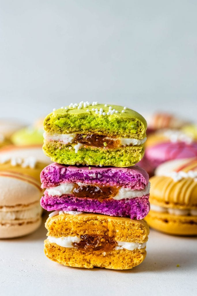 Colorful macarons, pink, red, yellow and white, with chocolate drizzle and sprinkles cut in half with apricot preserves filling.