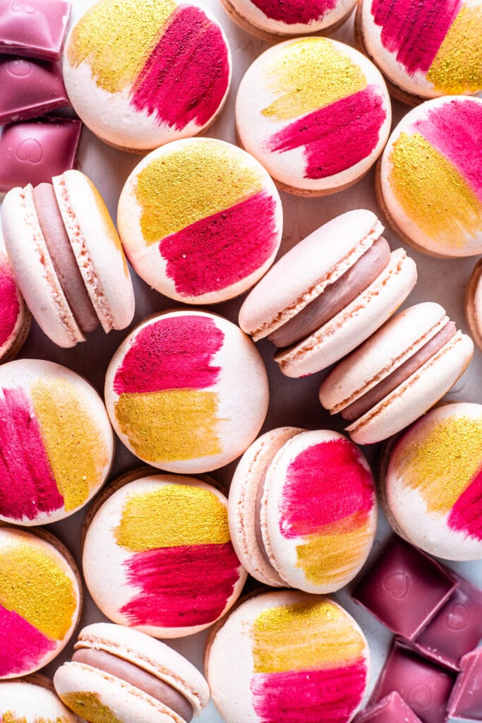 pink macarons with the shells painted with gold and pink, filled with ruby chocolate ganache.