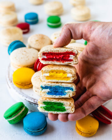 hand holding 4 macarons sliced in half, each has a different color in the center, red, yellow, blue and green, and on the background there are several white macarons, as well as blue, yellow, red, and green ones.